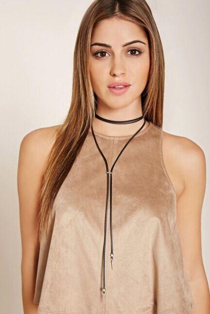 Modelo usa colar de couro de duas voltas com blusa nude.