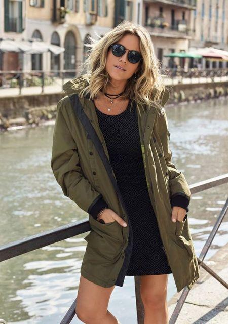 Modelo usa vestido preto, casaco militar verde e óculos escuros preto.