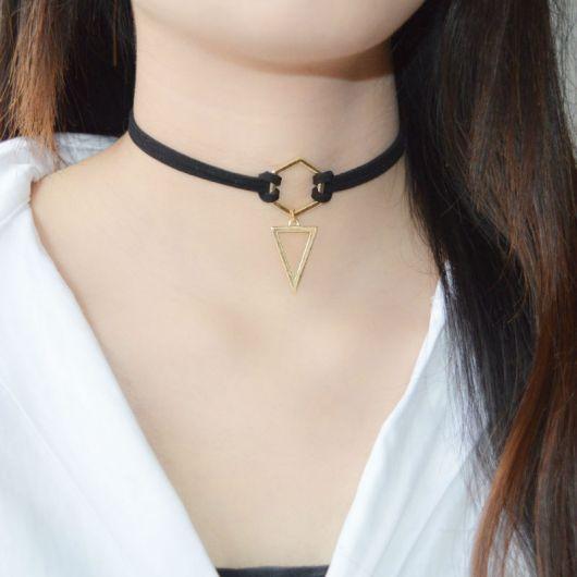 modelo usa blusa branca, pingente triangular e redondo.