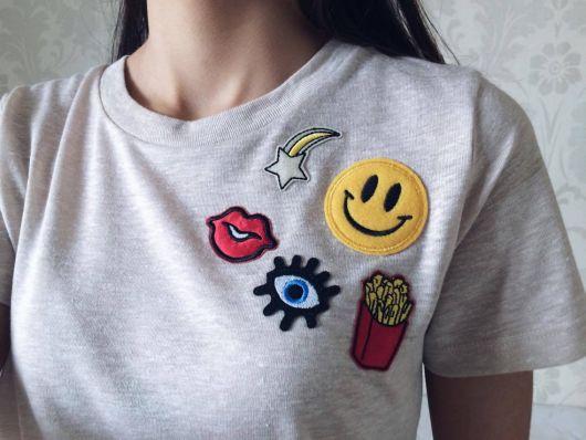 Modelo veste camiseta cinza básica com patches de olho, boca, batata frita e emoji sorrindo.