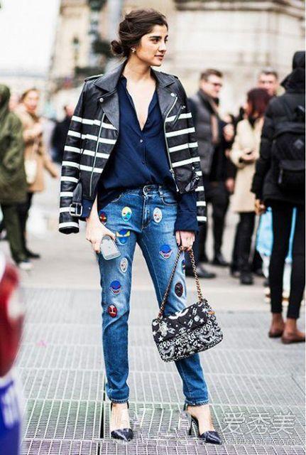 Modelo usa camisa azul marinho, calça jeans com patches, jaqueta de couro preta com listras brancas e sapato scarpin azul marinho com bolsa preta alça média.