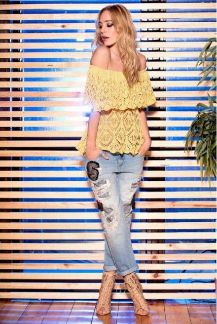 Modelo veste calça jeans desbotada, blusa ombro a ombro em renda amarela e scarpin.