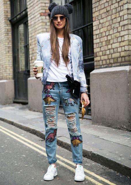 Modelo usa tênis branco, calça jeans com patches, blusa branca e blazer azul clarinho.