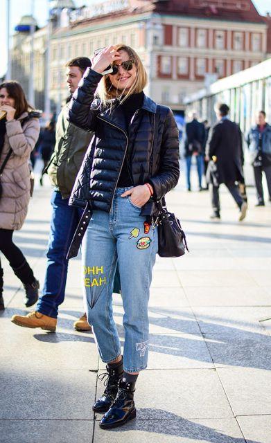 Modelo usa cuturno preto, jaqueta, bolsa e blusa preta com calça jeans de patches.