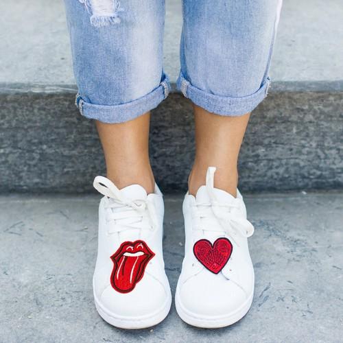 Modelo usa calça cigarrete jeans com tenis branco de patches com emblemas de boca e coração vermelho.
