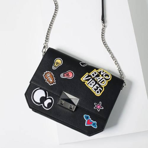 Bolsa preta pequena com patches e alça longa de corrente.