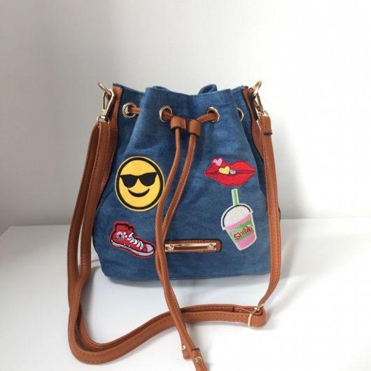Modelo de bolsa jeans com alça caramelo modelo saco com detalhes de patches coloridas e divertidas.