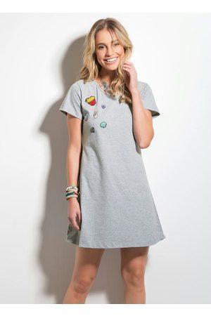 Modelo usa vestido cinza estilo camiseta com patches de batata frita.