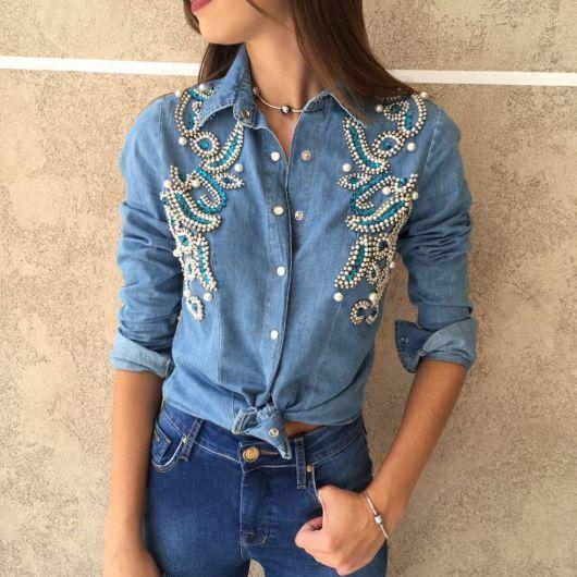 Modelo veste jaqueta jeans customizada com pedras na frente, na cor azul e branco.