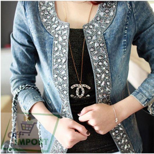 Modelo veste jaqueta jeans customizada com pedras, bolsa de alça corrente, calça jeans e blusinha preta com colar de brilhantes chanel.