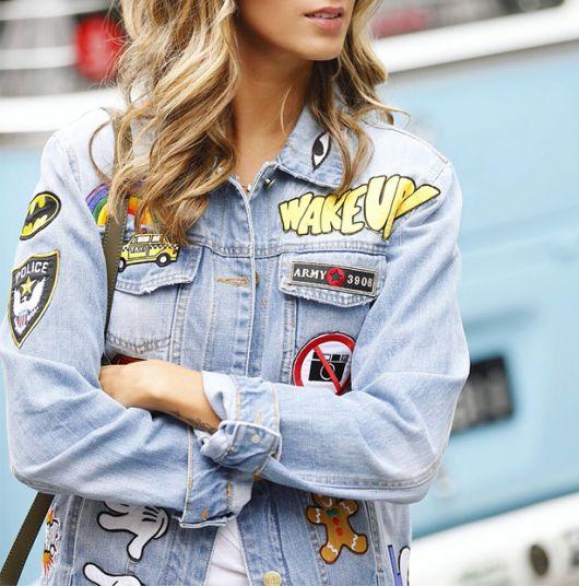 Modelo usa jaqueta azul clara quase cinza (desbotada) com trabalhado de colagem com patches.