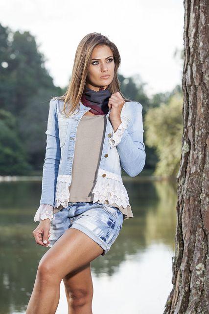 Modelo usa jaqueta jeans customizada com renda branca, short jeans, blusa cinza e cachecol.