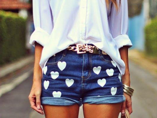 Modelo usa camisa branca, cinto marrom e short jeans de coração customizado.