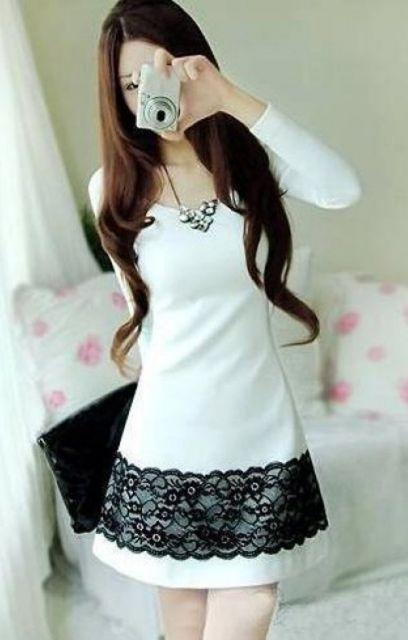 Modelo usa vestido branco manga longa com renda preta.