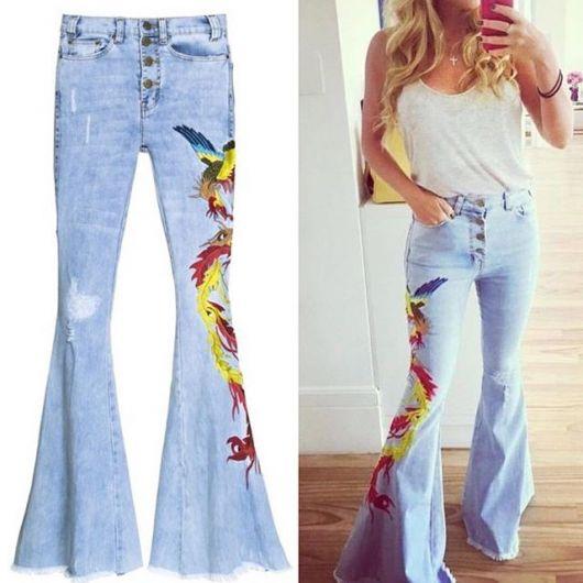 Modelo usa look com calça jeans flare azul claro com blusinha de alçinha branca.