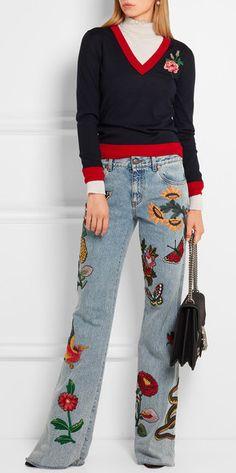 Modelo usa calça jeans com bolsa preta e moletom manga longa preto com vermelho.