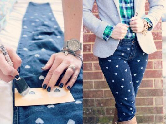 Modelo usa calça jeans azul customizada com corações brancos, blusa xadrez e blazer azul.