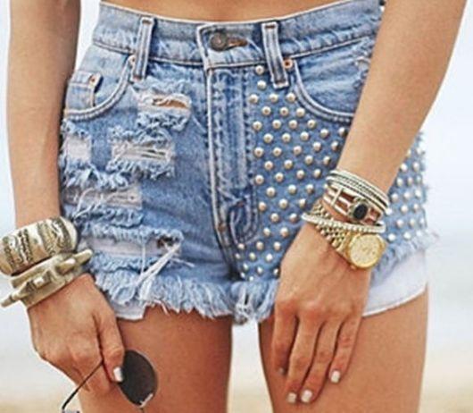 Modelo usa short jeans azul claro com spikes do lado e detalhes destroyed.