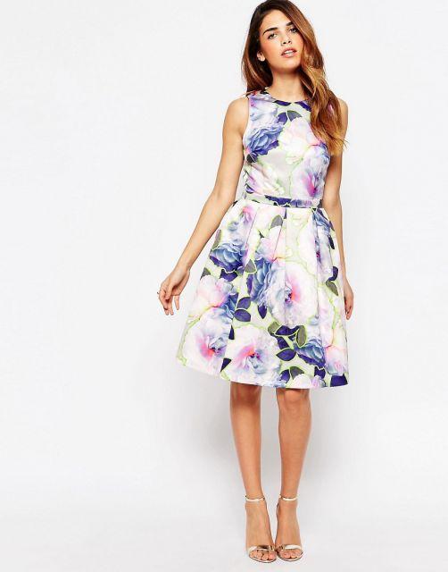 Modelo usa vestido floral branco com flores azul e rosa com sandalia nude.