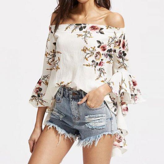Modelo usa short jeans com blusa branca ombro a ombro com estampa floral miudinha.