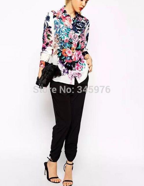 Modelo usa calça preta, sandalia na mesma cor, camis branca estampa floral e clutch preta.