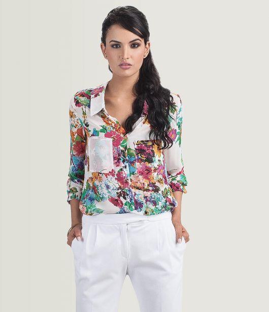 Modelo usa calça branca, camisa branca estampa floral.