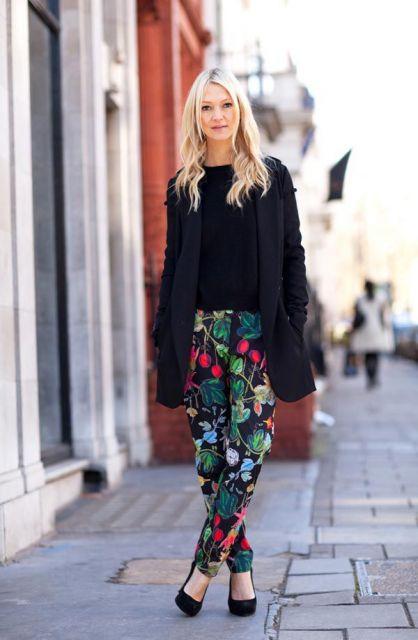 Modelo usa sobre tudo preto, blusa preta, calça estampada floral e sapato preto de salto.