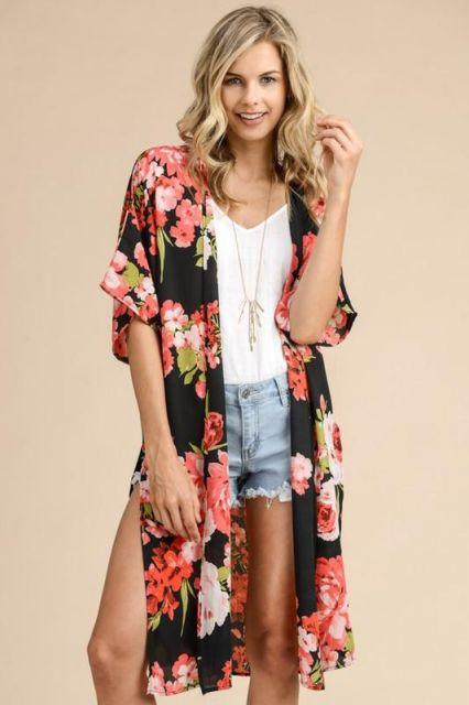 Modelo usa bermuda jeans, blusa branca e kimono preto estampado floral em preto e vermelho e branco.