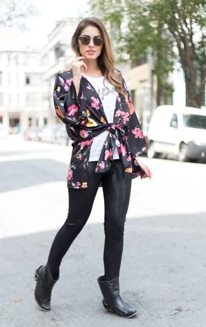 Modelo usa calça de couro preta, blusa branca, kimono preto com florais cor de rosa e botinha preta.