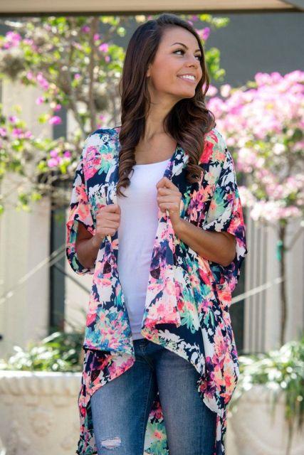 Modelo usa calça jeans, blusa branca e kimono estampado floral nas cores rosa e azul.