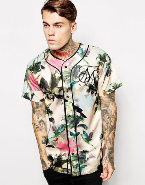Modelo usa camisa floral manga curta nas cores amarelo claro, verde , azul e rosa com calça jeans desbotada.