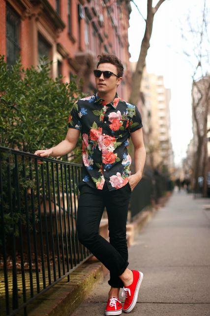Modelo usa calça jeans preta, camisa estampa floral nas cores preto , verde e vermelho.
