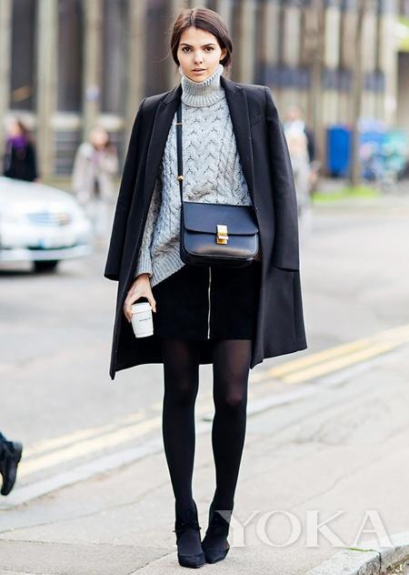 Modelo veste look com saia preta, blusa de gola cinza, casaco preto, meia preta transparente e ankle boot.