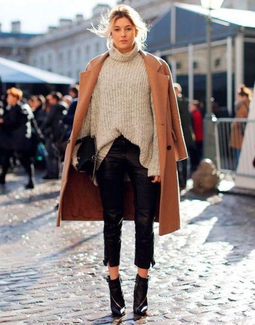 Modelo usa blusa sueter bege gola alta, casaco caramelo comprido, calça preta justinha e bota preta cano curto.
