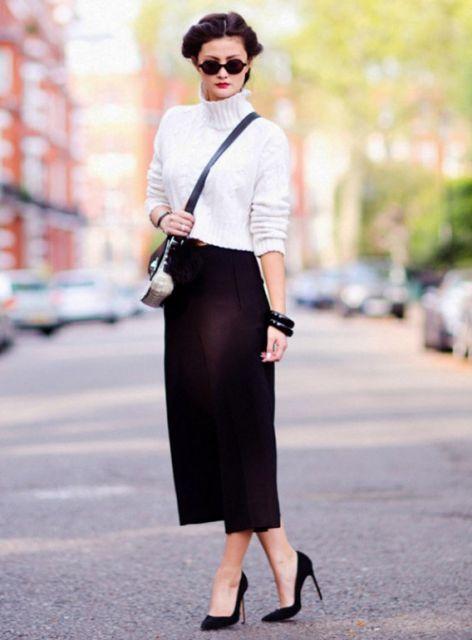 Modelo usa calça pantacourt preta sapato e bolsa na mesma cor e blusa branca.