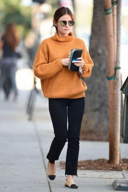 Modelo usa calça jeans preta, sapatilha preta e blusa gola role caramelo.