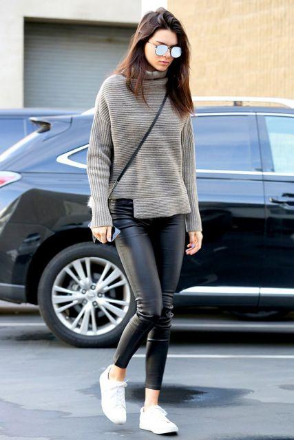 Modelo usa calça preta de couro, blusa cinza gola alta e tenis.