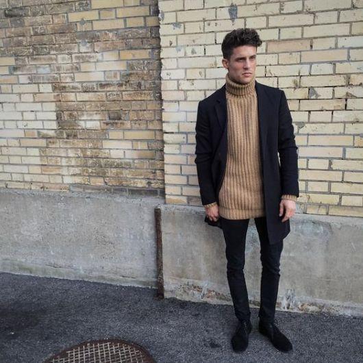 Modelo usa calça preta, blazer preto e blusa gola rolê bege e sapato preto.