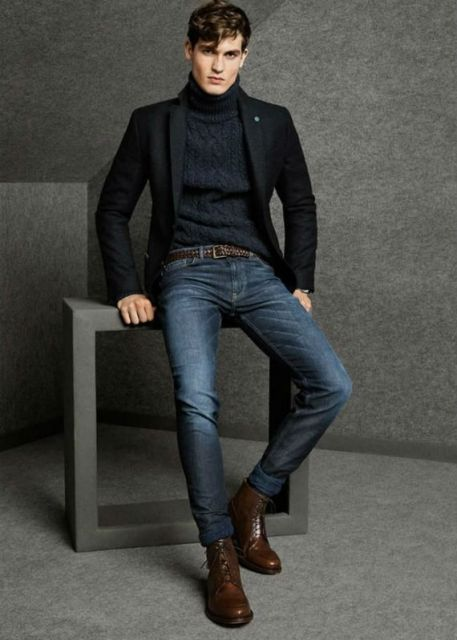 Modelo usa blusa preta, calça jeans, blazer e sapato marrom de couro.