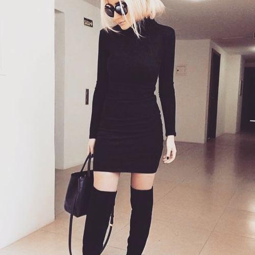 Modelo usa vestido de malha gola rolê preto e bota cano longo na mesma cor.