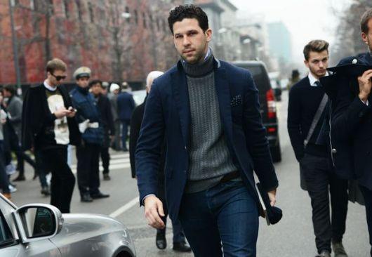 Modelo usa calça jeans azul escuro, blusa gola alta cinza chumbo e blazer azul escuro marinho.