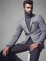 Modelo veste blazer cinza, blusa cinza gola alta e calça alfaiataria na mesma cor.