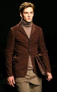 Modelo veste calça bege, blazer marrom e blusa bege.