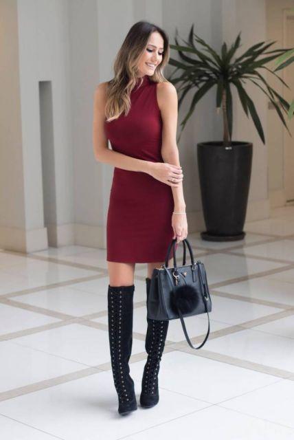 Modelo usa vestido vermelho gola rolê sem mangas com bota cano longo.