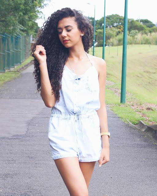 Modelo usa macquinho branco de alcinhas jeans com cabelos soltos..