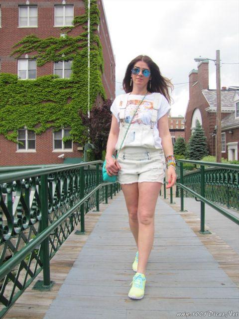 Modelo usa camisetinha estampada, macaquinho jeans branco, bolsa verde agua e tenis branco.
