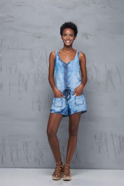 Modelo usa macquinho jeans azul claro com bolsos e sandalia plataforma, cor caramelo.