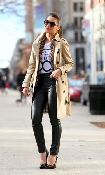 Modelo usa calça preta, blusa branca estampada e sapato preto com trench coat (casaco) bege.