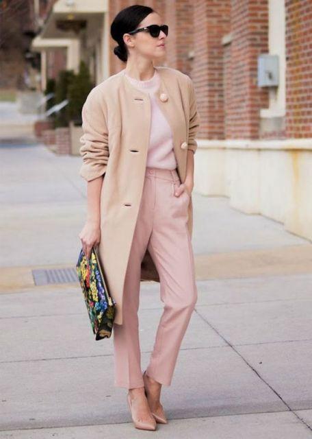Modelo usa calça rosa clarinho, blusa na mesma cor, casaco trench coat bege claro puxado pra cor (rosê), scarpin nude e bolsa preta de mão com detalhes coloridos.