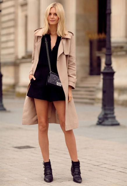 Modelo usa trench coat bege escuro, vestido preto, bolsa pequena corrente e botinha preta.